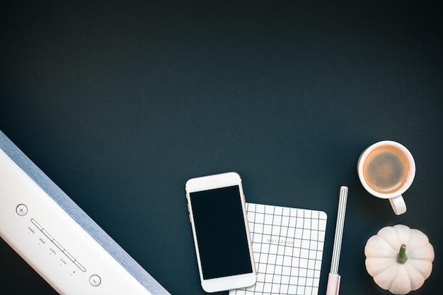 サウンドバー携帯電話とコーヒーカップ付きのテーブル