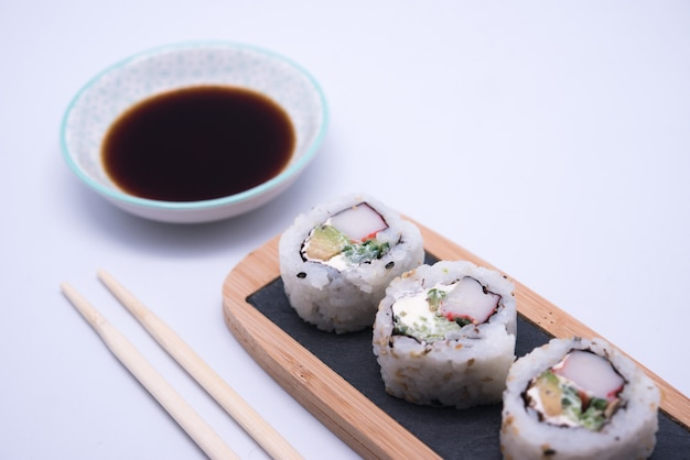 Table with sushi and chopsticks with bowl of soy sauce