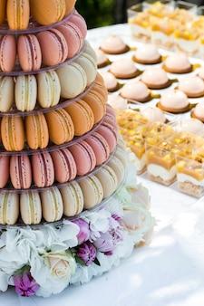 Стол со сладостями, украшенный цветами и макарунами