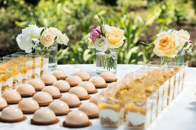 꽃과 마카롱 케이크로 장식 된 과자 테이블