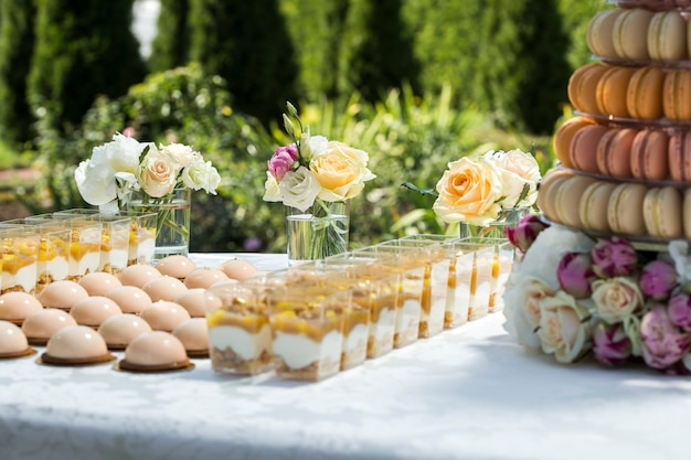 Table with sweets decorated with flowers and macaroon cakes and light desserts in cups