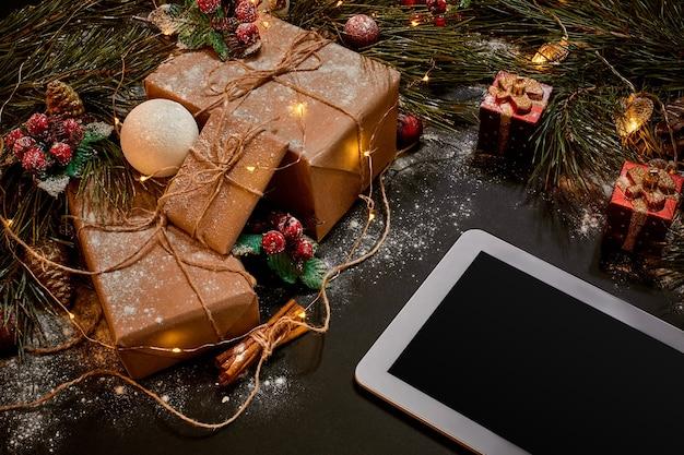 태블릿 컴퓨터, 크리스마스 장난감, 별, 푹신한 전나무 가지가 있는 테이블. 텍스트를 위한 여유 공간입니다. 평면도. 공간을 복사합니다. 확대