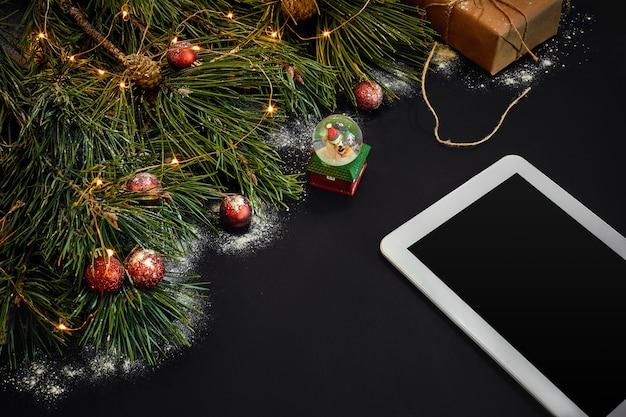 태블릿 컴퓨터 크리스마스 장난감 별과 푹신한 전나무 가지가 있는 테이블에는 텍스트 위쪽 보기를 위한 여유 공간이 있습니다.