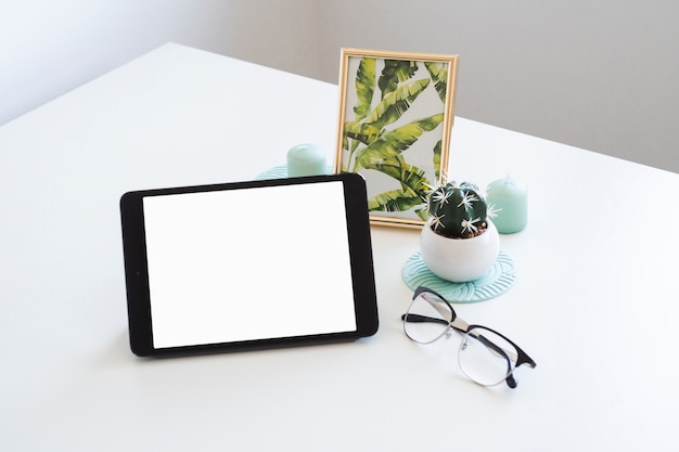 Table with tablet near photo frame and eyeglasses