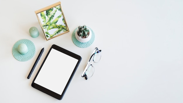 Table with tablet near photo frame, houseplant, pen and eyeglasses