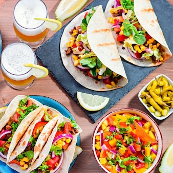 Table with tacos, mango salsa, nachos with sauce, guacamole, lemon beer for cinco de mayo celebration party. appetizers and traditional mexican dishes for family dinner on wooden table, space for text