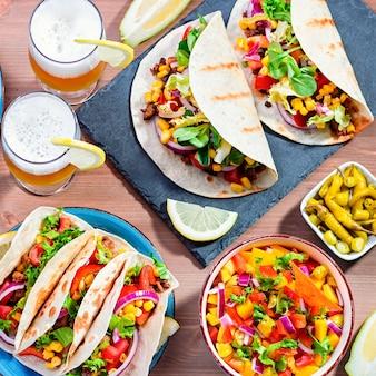 タコス、マンゴーサルサ、ナチョスとソース、ワカモレ、シンコデマヨのお祝いパーティー用のレモンビールのテーブル。木製のテーブルでの家族の夕食のための前菜と伝統的なメキシコ料理、テキストのためのスペース