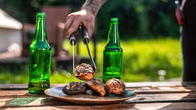 Table with two bottles of beer, man putting meat on a plate. glamping, greenery