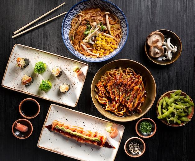 典型的な日本食の寿司、サーモンのたたき、味噌汁、カリカリのチキン ヌードル、枝豆のテーブル。上から見た。