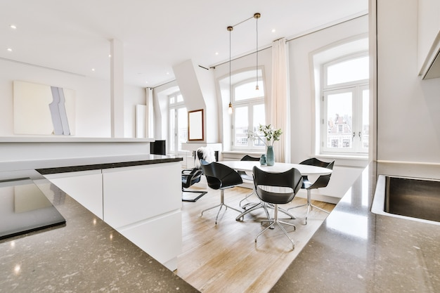 Table with vases and chairs located near kitchen counters in modern light flat
