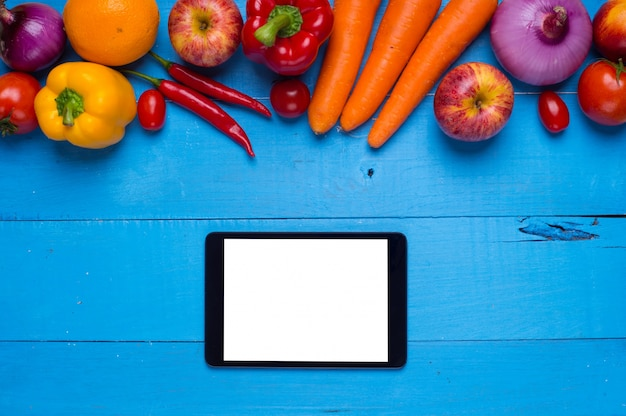 Table with vegetables and a tablet