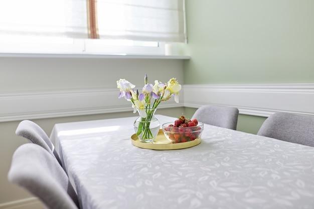 Стол с белой скатертью, букет цветов ирисов в вазе и поднос со спелой клубникой