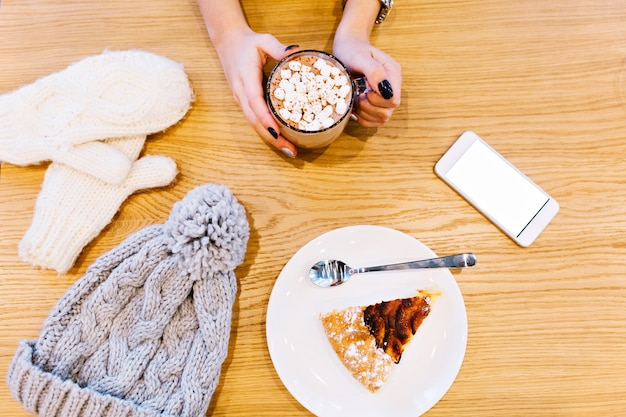 Table with white winter gloves, phone, hot chocolate holding by girl and piece of pie, knitted grey hat.
