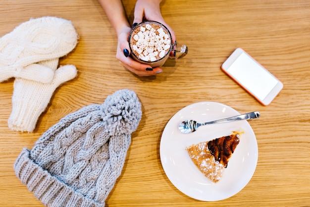 Tavolo con guanti invernali bianchi, pezzo di torta, cappello lavorato a maglia, telefono e cioccolata calda nelle mani della ragazza.