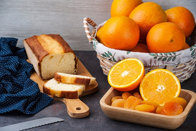 Table with whole and sliced oranges, dried apricot and orange cake on a kitchen board.