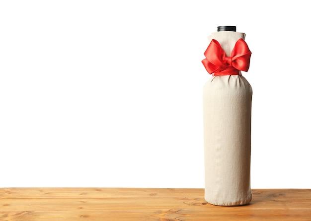 Стол с бутылкой вина в подарочном пакете на белом фоне