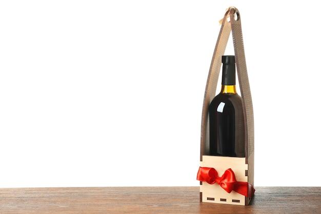 Стол с бутылкой вина в подарочной коробке на белом фоне