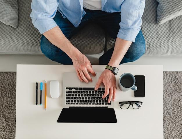 テーブルの職場のクローズアップの男の手は、ラップトップで入力して自宅で作業しています