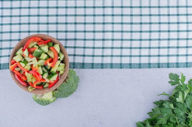 Tovaglia, ciotola di insalata di verdure, fascio di prezzemolo e broccoli su sfondo marmo.