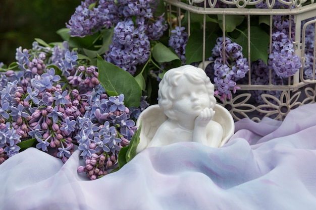 On a tablecloth a cage with a lilac and a statue of a white angel