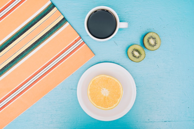 Tablecloth; coffee cup; halved kiwi and orange fruit on blue backdrop