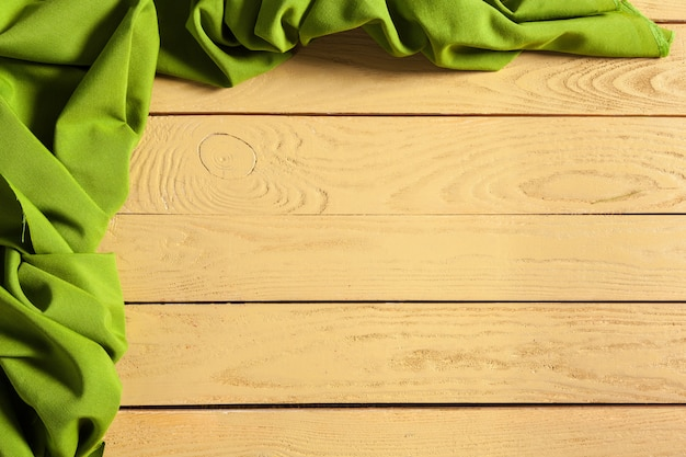 Tablecloth and green textile on wooden background