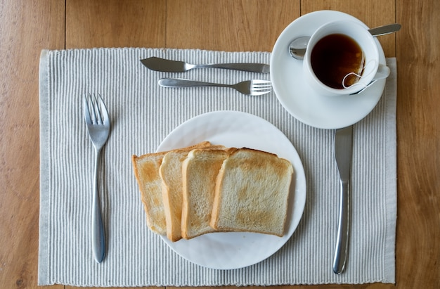 Tablecloth slice bread on white plate and tea cup