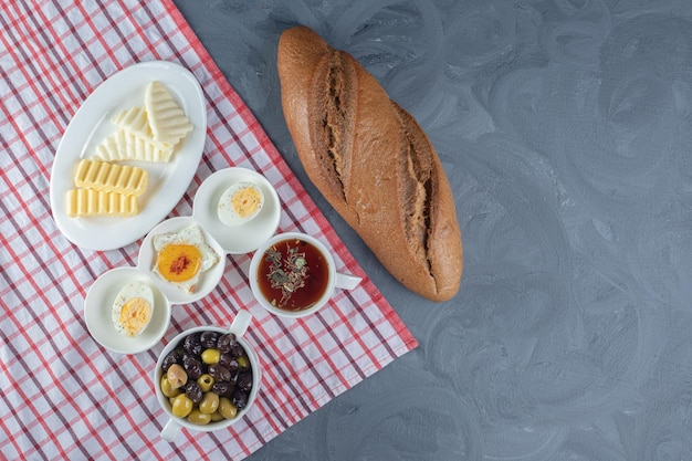 Tablecloth underneath a breakfast bundle of bread loaf and platters of cheese, butter and egg, with tea and olives on marble background.