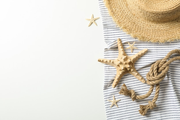Tablecloth with straw hat, starfishes and sea rope on white background, space for text and top view. summer vacation