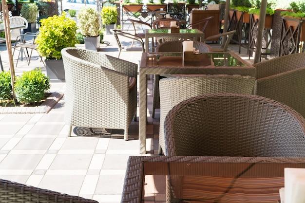 花壇のある屋外サマーカフェのテーブルと籐の椅子