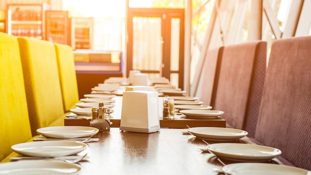モダンなカフェテリアで食事をするためのテーブルセット。宴会テーブルにたくさんの白いセラミックプレート。人々のグループのために提供されるテーブル。現代の学校のきれいな食堂。ランチルーム。