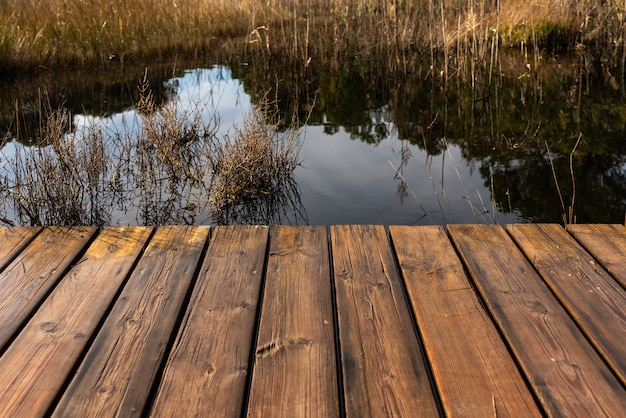 Tables of a wet wooden bridge over a lake.