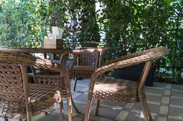 Tables and wicker chairs in outdoor summer cafe with flower beds