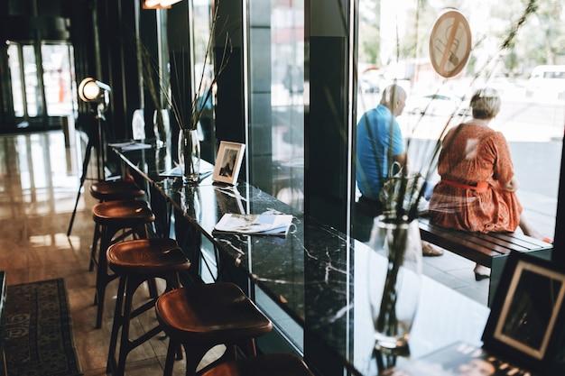 유리벽 옆에 의자가 있는 테이블이 표시됩니다. 러블리한 분위기의 커피숍이 보입니다.
