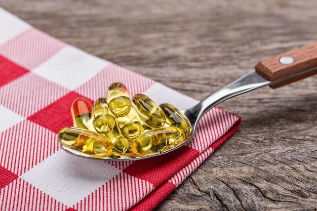 Столовая ложка с диетическими таблетками витамина е. в декоративной салфетке.