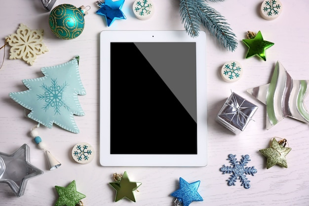 흰색 표면 나무 표면에 태블릿 및 크리스마스 장식