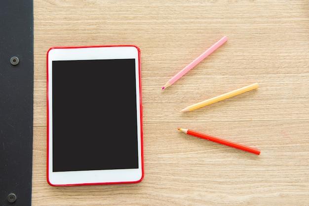 木製のテーブルにタブレットと色鉛筆。