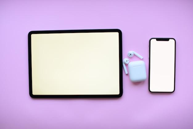 ピンクの背景にタブレットとlとエアポッド