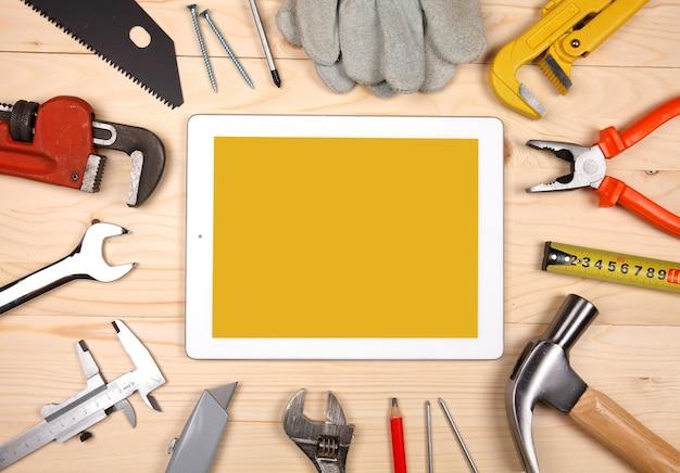 タブレットと配管のセットと木製の背景に衛生工学作業のためのツール