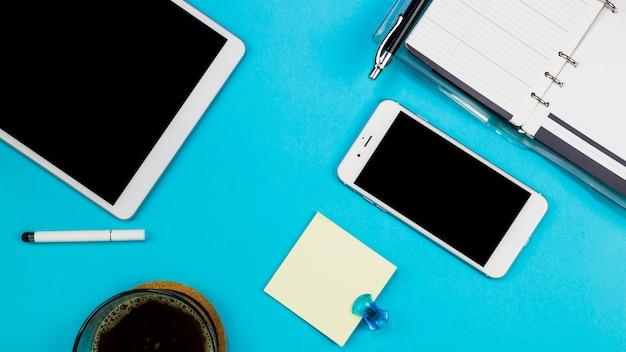 タブレットとスマートフォンのテーブルの上のノートブック