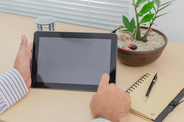 Планшет в офисе с ноутбуком и заводом