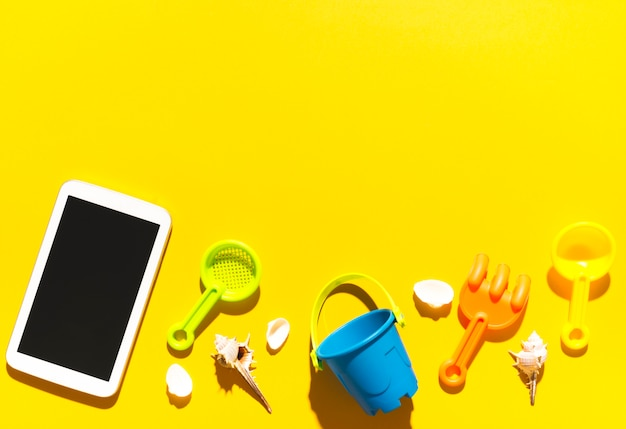 Tablet and beach toys on colorful surface