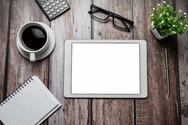 木製の机の上のコーヒーノートブック眼鏡計算機とタブレット空白の白い画面
