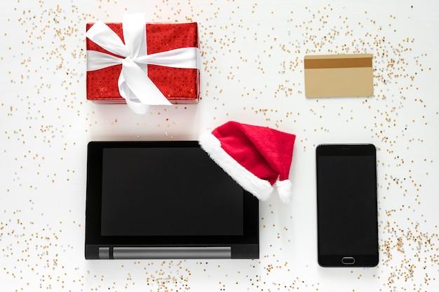 Планшет, сотовая связь, кредитная карта и подарочная коробка с золотым конфетти