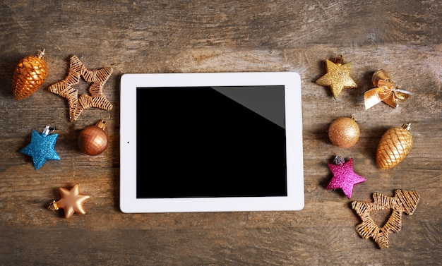 Tablet and christmas decor on wooden background