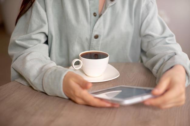 Планшет крупным планом фото с женщиной в повседневной одежде дома или в кафе и пить кофе