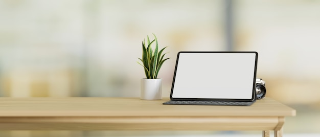 Tablet computer blank screen mockup stand on wood table with copy space blurred background