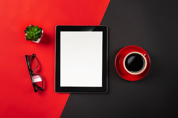 Tablet computer gadget on businessman desk and coffee cup. top view with copy space