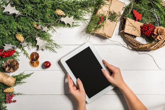Планшетный компьютер в руках человека. рядом столик с подарочной коробкой планшетного компьютера, рождественским колокольчиком и пушистыми еловыми ветками. свободное место для текста. вид сверху. скопируйте пространство. крупным планом