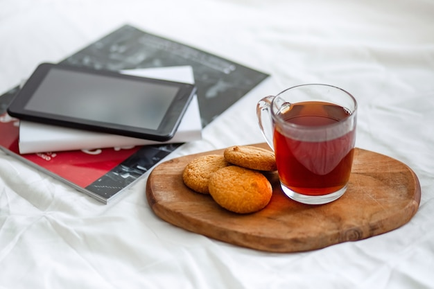 A tablet computer, a magazine, and a book on the bed.
